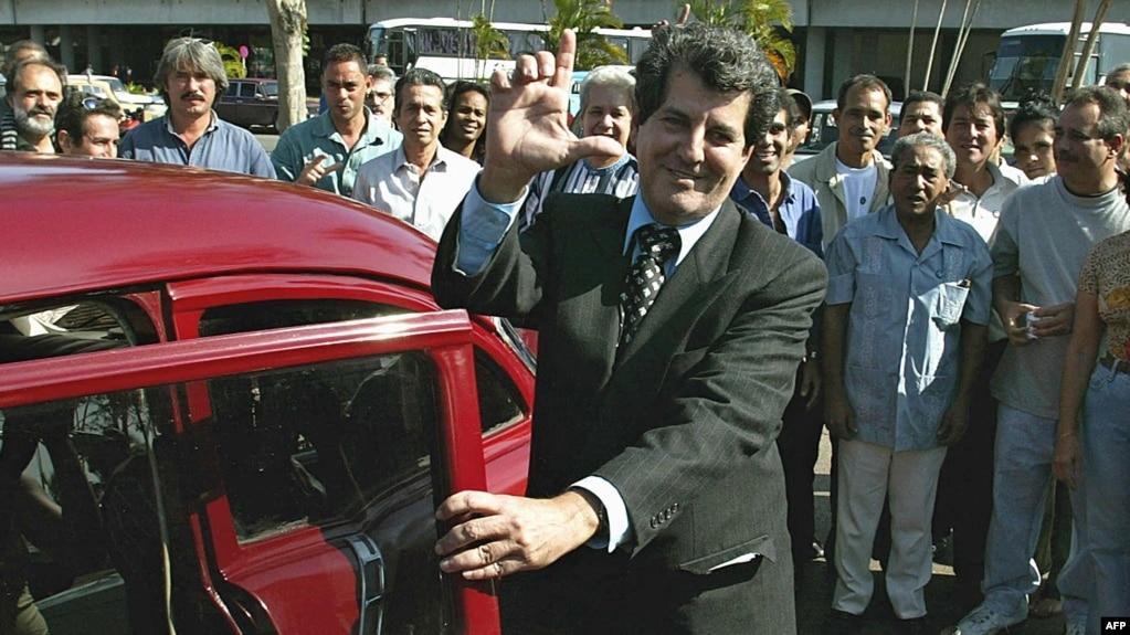 """Oswaldo Payá hace la """"L"""" de liberación tras su arribo al aeropuerto Jose Martí de La Habana, el 2 de febrero de 2003, tras un viaje a Europa para recibir el premio Sájarov."""