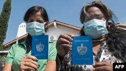 Inmigrantes cubanas muestran sus pasaportes mientras protestan frente a la agencia de la ONU para refugiados en Costa Rica. Ezequiel BECERRA / AFP