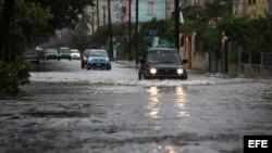 Vehículos transitan por una calle inundada hoy, viernes 29 de noviembre de 2013, en La Habana