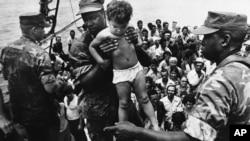 Un marine de EEUU ayuda a desembarcar a un niño cubano tras su llegada a las costas de Florida en el éxodo del Mariel. AP Photo/Fernando Yovera)