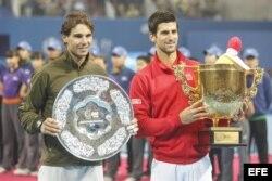 Novak Djokovic de Serbia (d) muestra el trofeo de campeón después de derrotar a Rafael Nadal de España (i) en la final individual masculina del Abierto de China, en el Centro Nacional de Tenis en Beijing.