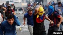 Manifestantes huyen durante un enfrentamiento con la fuerzas de seguridad durante una protesta en Caracas el 30 de abril de 2019.