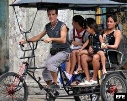Dos mujeres viajan con sus hijas en un bicitaxi.