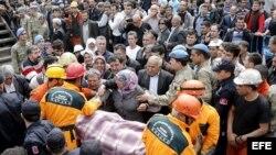 Una multitud de familiares y amigos de los mineros atrapados y desaparecidos en una explosión en una mina en Soma lloran desconsolados mientras los equipos de rescate evacúan un cuerpo en la provincia de Manisa en Turquía .
