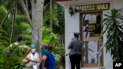 Varias personas permanecen afuera de una oficina de la Western Union, en el Vedado, La Habana. (AP/Ismael Francisco)