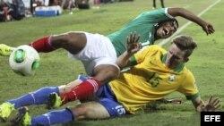 El jugador brasileño Leo Pereira (d) lucha por el balón con el mexicano Marco Granados durante el partido Brasil-México, de cuartos de final del Mundial sub-17 de fútbol, en el estadio Al-Ahli's de Dubai, Emiratos Árabes Unidos.