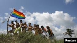 Un grupo de hombres posa con la bandera del movimiento gay en una playa de Cuba.