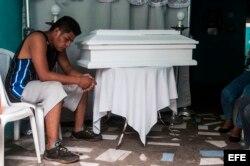 Nelson Gabriel Lorio permanece junto al ataúd de su hijo, Leonardo Lorio, de 14 meses, en su casa en Managua.