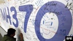 Un hombre escribe mensajes en honor a las víctimas del vuelo MH370 de Malaysia Airlines en el aeropuerto internacional de Kuala Lumpur (marzo, 2014).