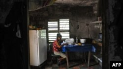 Una señora escoge arroz en su casa en El Caney, Santiago de Cuba el 21 de junio de 2017.