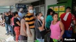 La gente espera en fila para comprar comida en un supermercado de Managua después de que el gobierno reportara el primer caso de COVID-19 en marzo de 2020.