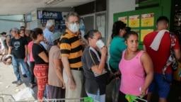 La gente espera en fila para comprar comida en un supermercado de La Habana.