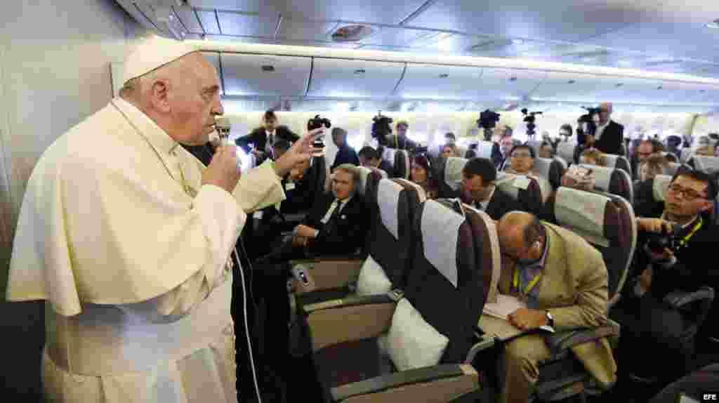 El papa Francisco (i) se dirige a los periodistas durante el vuelo del Boeing 777 de la compañía Korean Airlines.