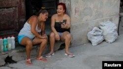 Dos mujeres cubanas conversan mientras chequean un mensaje en el celular.