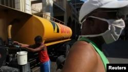 Cubanos almacenan agua en La Habana en medio de la crisis por el coronavirus. Las autoridades están amenazando y multando a miembros de la sociedad civil que reporten sobre la situación de la pandemia en la isla.
