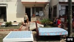 Vecinos de un barrio afectado por las inundaciones sacan sus colchones a secar al sol tras el paso del huracán Irma.