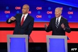 El ex vicepresidente Joe Biden (derecha) y el senador de Nueva Jersey Cory Booker en un momento del debate del miércoles en el Teatro Fox de Detroit (Foto: Jim Watson/AFP).
