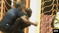 Un rehén herido es trasladado por personal militar de Mali a su salida del hotel de lujo Radisson Blu. EFE