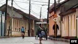 """Una mujer camina por las calles de la ciudad de Baracoa, hoy, martes 04 de octubre, en Guantánamo (Cuba). El """"extremadamente peligroso"""" huracán de categoría 4 Matthew."""