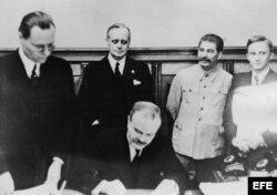 Moscú, 23-8-1939.- Viacheslav Molotov, ministro de Asuntos Exteriores de la URSS, firma en Moscú el pacto de No Agresión entre Alemania y la Unión Soviética. Tras él, su homólogo alemán, Joachim von Ribbentrop, y al lado de éste, Josef Stalin (2º d.)
