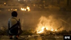 20/02/2014.- Un hombre permanece junto al fuego de las barricadas durante una protesta contra el Gobierno del presidente venezolano
