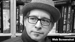 Michael H. Miranda con libros y sombrero.