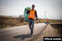 Yaster (frente) y Raúl cargan bolsas con desechos a un punto de recolección. © ACNUR/Radonja Srdanovic