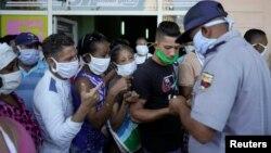 Un policía organiza una fila de personas que esperan para comprar alimentos en La Habana, el 3 de abril del 2020.