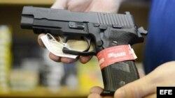Un propietario de una armería muestra una pistola semiautomática Sig Sauer en su negocio.