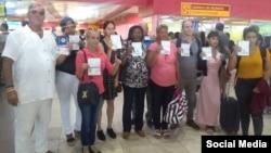 Activistas regulados muestransus pasaportes con la negativa de viaje, en el Aeropuerto José Martí de La Habana.
