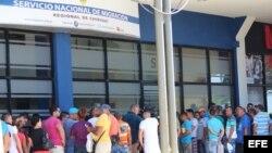 Migrantes cubanos esperan hoy, domingo 21 de febrero de 2016, a las puertas de la oficina de Migración de David, para recibir en sus pasaportes un permiso migratorio para poder salir legalmente de Panamá hacia México, desde donde cruzarán a Estados Unidos