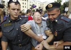 Oficiales de la policía rusa detienen a un manifestante durante una protesta cerca del juzgado donde se dicta sentencia contra las integrantes del grupo punk ruso Pussy Riot.