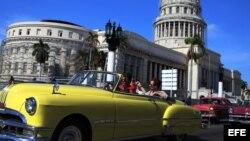Dos turistas viajan en un viejo auto descapotable por una calle de La Habana Vieja. (Archivo)