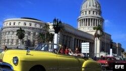 Dos turistas viajan en un viejo auto descapotable por una calle de La Habana.