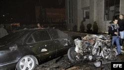 Fotografía cedida facilitada por la agencia siria de noticias SANA que muestra a unos policías sirios inspeccionando el lugar donde se ha registrado un atentado con coche bomba ante la sede del Ministerio del Interior sirio en Damasco, Siria.