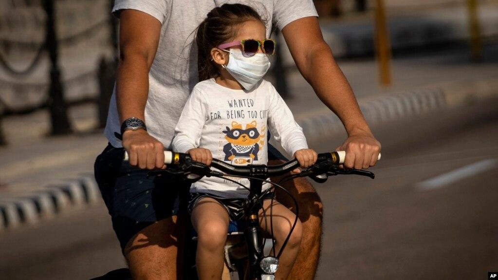 Un padre lleva a su hija en bicicleta por una calle de La Habana. (AP/Ramón Espinosa)
