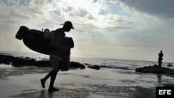 Archivo. Un pescador se dirige hacia el mar con sus utensilios de trabajo en una de las costas del litoral norte habanero.