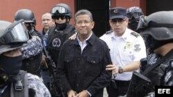 Agentes de la Policía Nacional Civil custodian al expresidente de El Salvador Francisco Flores (c) durante su traslado a una celda policial hoy, viernes 19 de septiembre de 2014, en San Salvador.