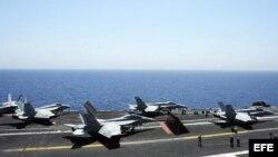 Miembros de la Marina guiando a varios aviones Hornet F/A 18 para su despegue desde la cubierta del portaaviones George H.W. Bush