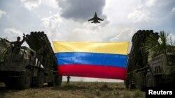 """Un avión de combate Sukhoi Su-30MKV de la Fuerza Aérea de Venezuela, de fabricación rusa, ondea una bandera venezolana atada a lanzamisiles durante el ejercicio militar """"Escudo Soberano 2015"""". (Archivo)"""
