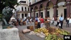 Varias personas compran alimentos en una feria organizada en el Paseo del Prado. Foto de archivo