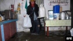 Un hombre trata de salvar algunas pertenencias en su casa inundada el jueves, 24 de mayo de 2012, en Yaguajay, provincia de Sancti Spíritus, Cuba.