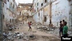 Niños juegan pelota en un edificio en ruinas en La Habana.