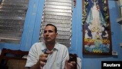 José Daniel Ferrer junto a una imagen de la Virgen de la Caridad del Cobre. (Reuters/Archivo)