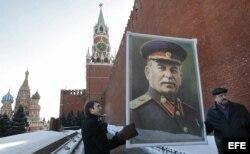 Un par de asistentes muestran un retrato del dictador soviético Iosif Stalin durante una ceremonia en recuerdo del 60º aniversario de la muerte del líder soviético en la plaza Roja de Moscú, Rusia.