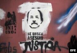 """Vista de una imagen del presidente Daniel Ortega pintada en una pared junto a la frase """"Se busca asesino""""."""