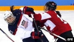 Catherine Ward (d), de la selección de Canadá, lucha por el disco con la estadounidense Hilary Knight (i) durante el partido Canadá-Estados Unidos.