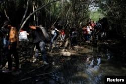 """Venezolanos atraviesan la frontera desde Colombia a través de una """"trocha"""" o sendero ilegal."""