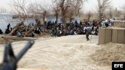 Militares afganos controlan a las personas que se han reunido frente a la base militar del distrito de Panjwai para protestar por el asesinato de 16 civiles afganos, el domingo, 11 de marzo de 2012.