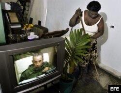 Archivo. Una mujer cubana limpia su casa mientras sigue por la TV la intervención especial de Fidel Castro.